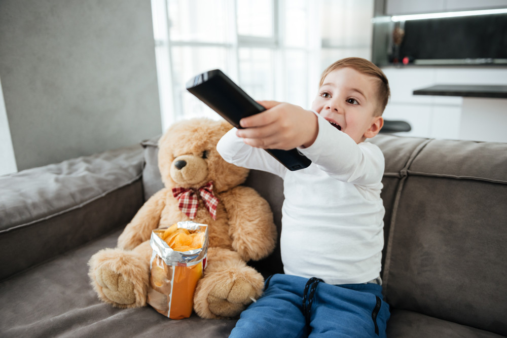 Picture of little boy sitting on sofa with teddy bear at home and watching TV while eating chips. Holding remote control.
