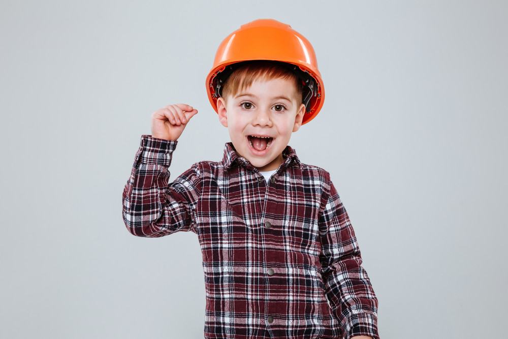 Picture of little cute child wearing helmet standing over grey background. Look at camera.