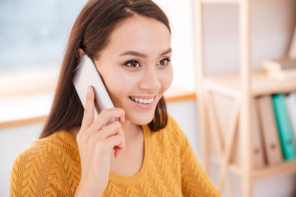 Picture of positive businesswoman dressed in sweater talking by her phone