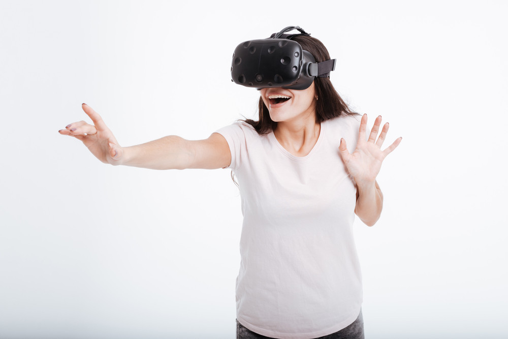 Picture of pretty cheerful lady wearing virtual reality device over white background.