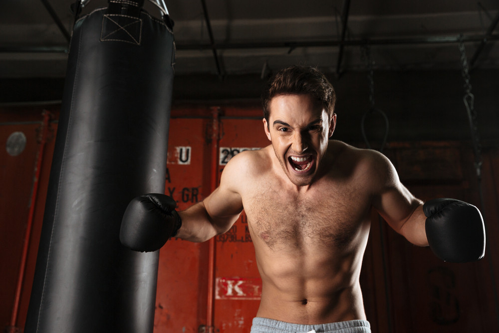 Picture of screaming agressive boxer training in a gym with punchbag. Looking at camera.