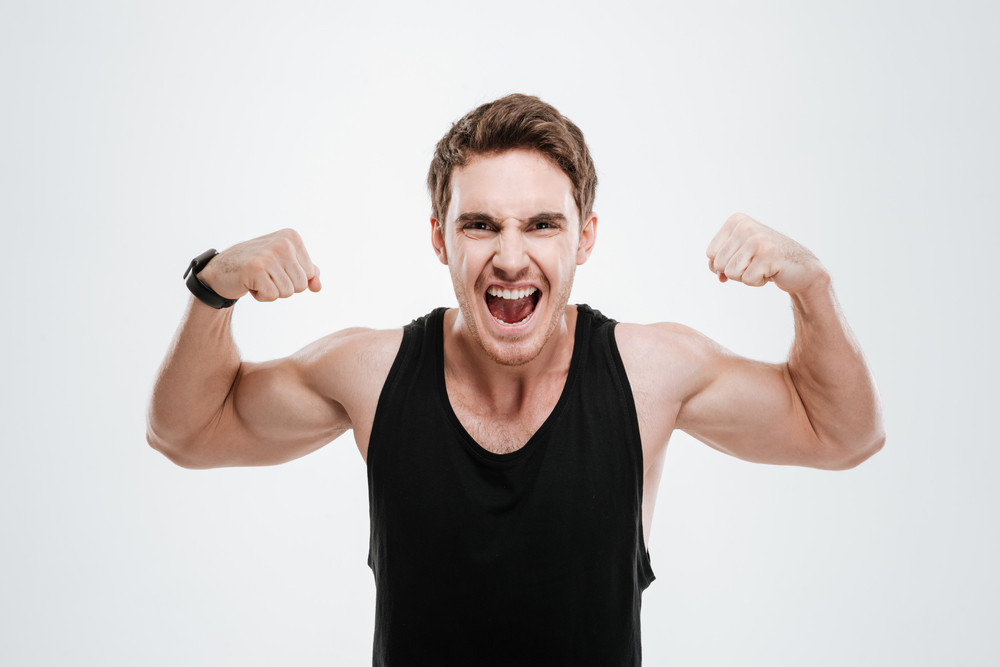 Picture of screaming young man dressed in black t-shirt standing over white background showing his biceps.