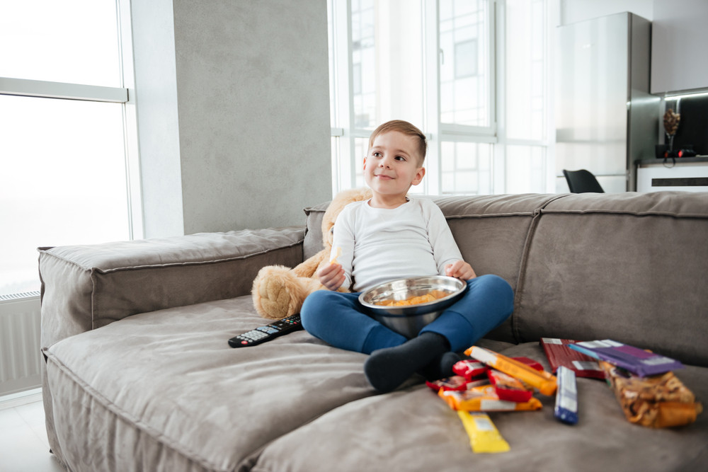 Picture of smiling boy on sofa with teddy bear at home watching TV while eating chips. Holding remote control.