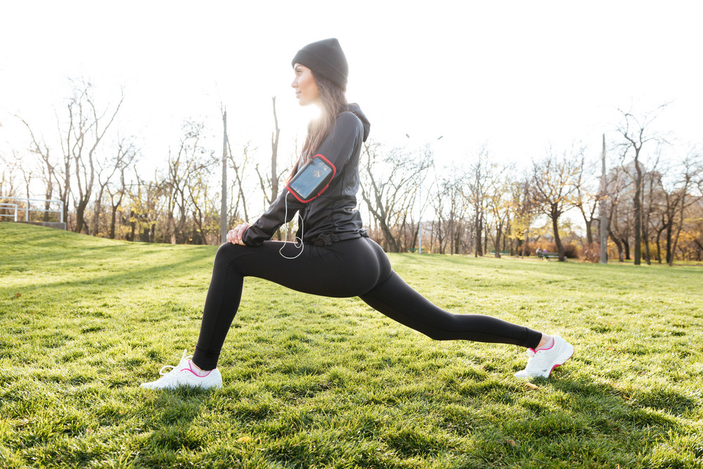 Picture of sport lady in warm clothes and headphones in autumn park make sport exercise