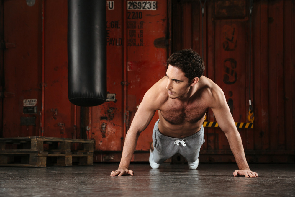 Picture of strong man make sport exercises in a gym. Looking aside.