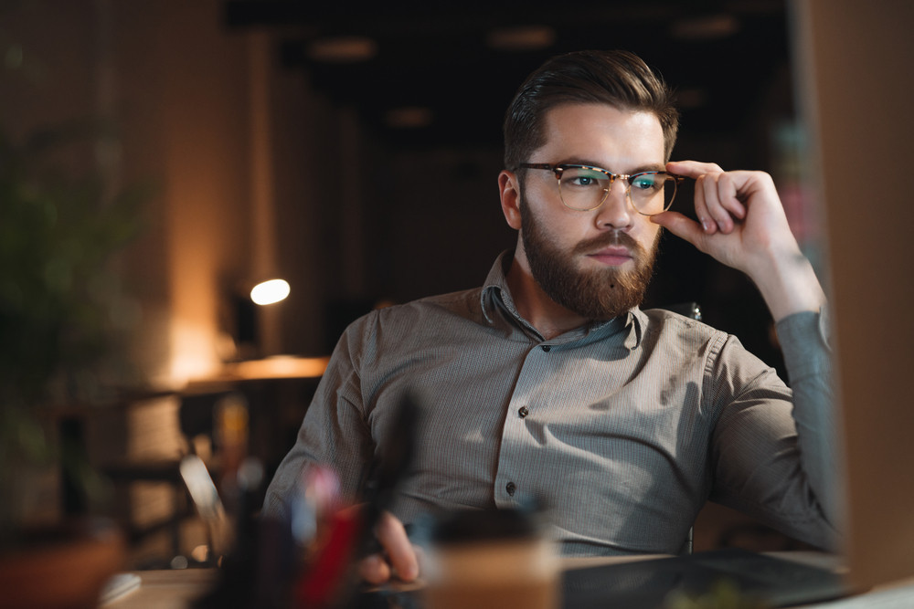Picture of web designer dressed in shirt and wearing eyeglasses working late at night and looking at computer. Touching glasses.