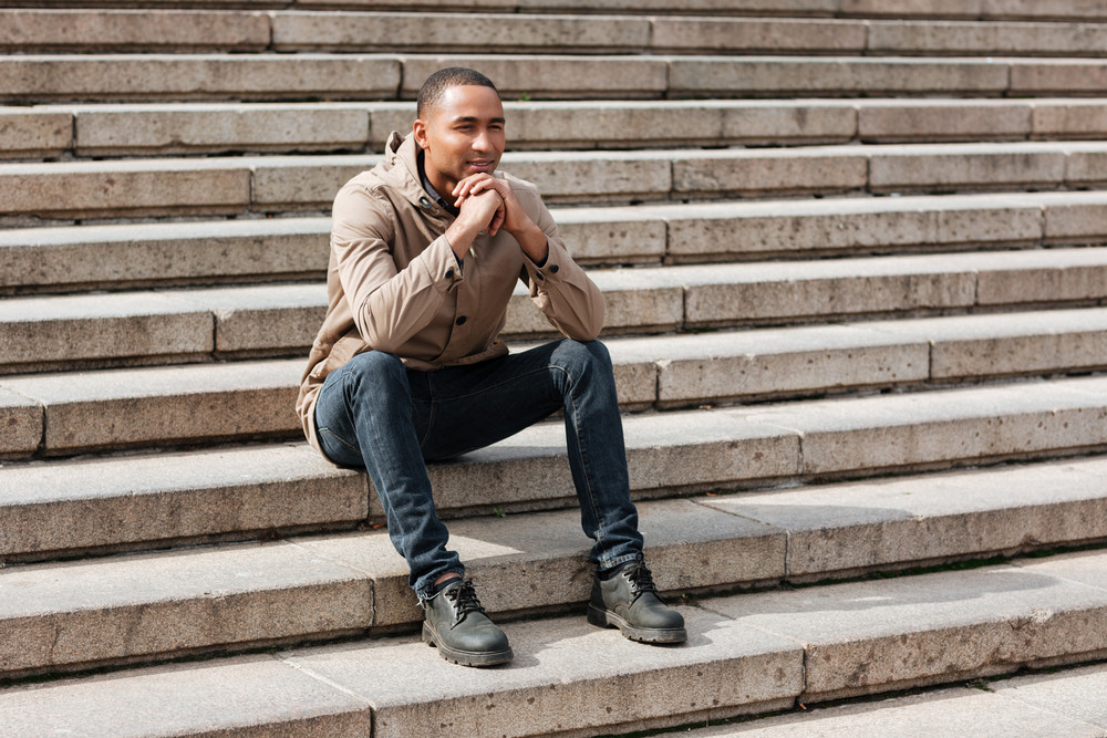 Picture of young african cheerful man sitting on staircase. Looking aside.