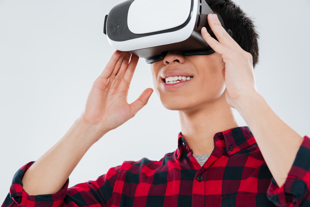 Picture of young asian man dressed in casual shirt in a cage and wearing virtual reality device. Isolated over white background.
