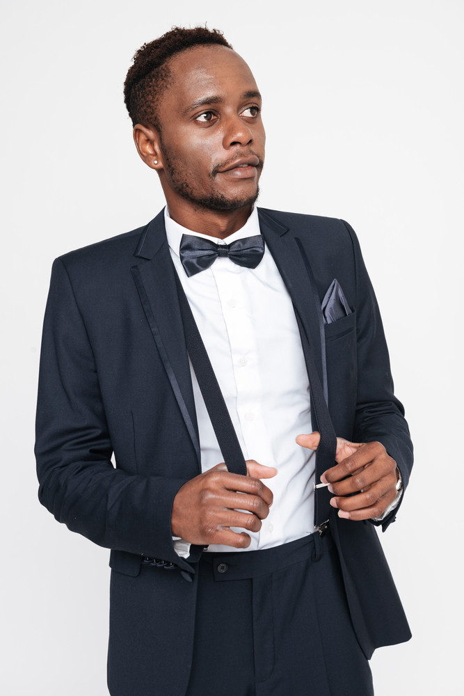 Picture of young attractive african businessman posing in studio. Isolated over white background. Look aside.