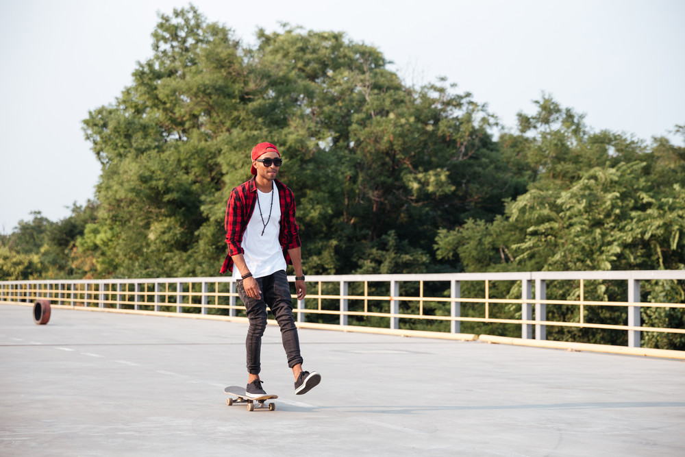Picture of young attractive dark skinned guy wearing sunglasses and cap skateboarding. Against the nature background.