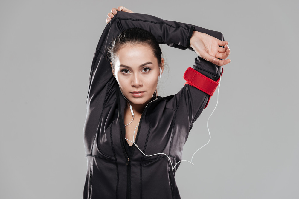 Picture of young attractive fitness lady make sport exercises over grey background listening music with earphones.
