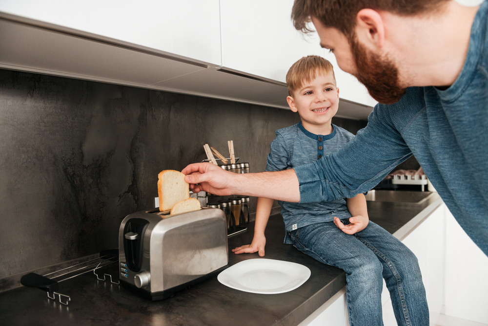 Picture of young bearded father dressed in blue sweater cooking at kitchen with his little cute son