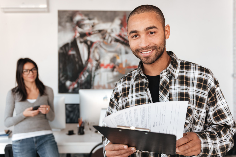 Picture of young business partners indoors. African man holding clipboard and look at camera. Focus on man.