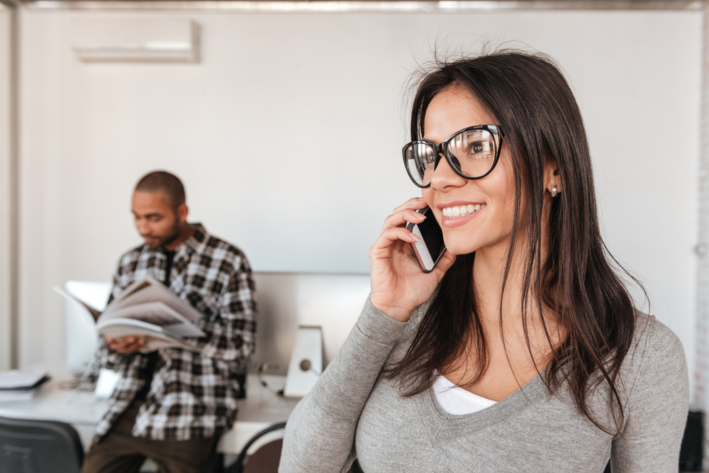 Picture of young business partners standing in office while man holding magazine and woman talking by phone. Focus on woman.