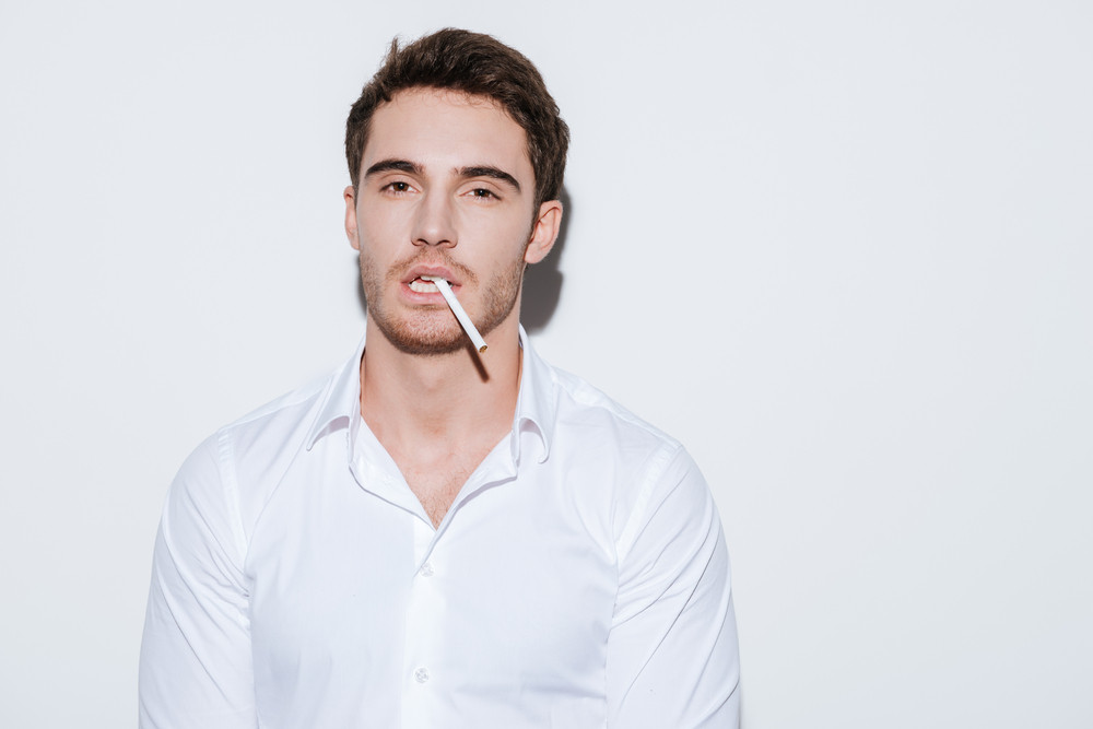 Picture of young businessman posing at studio and look at camera while holding cigarette. Isolated over white background.