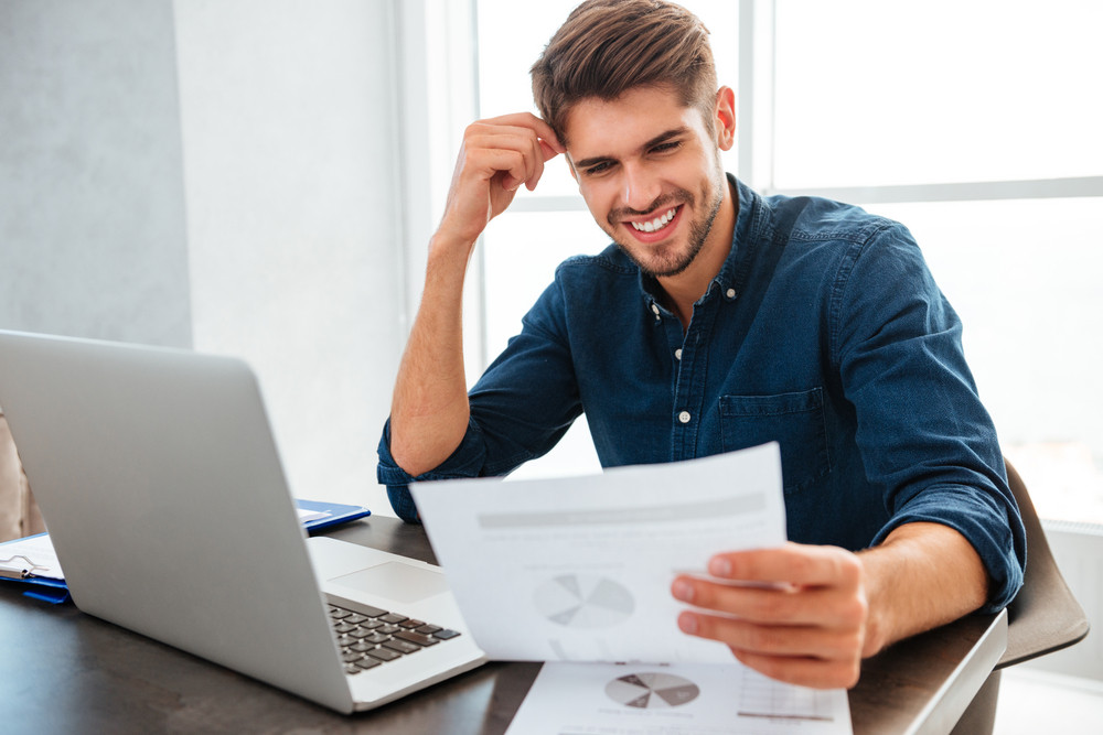 Picture of young cheerful man analyzing finances while sitting at the table while looking at the papers.