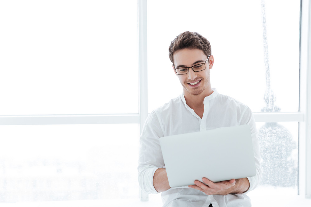Picture of young cheerful man dressed in white shirt using laptop computer near big white window.