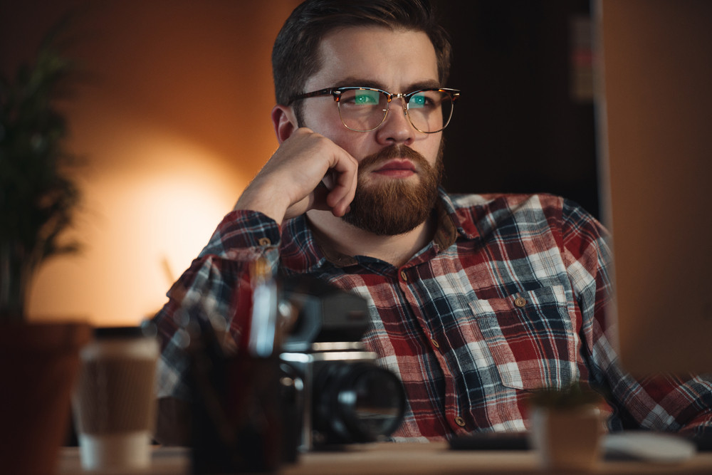 Picture of young concentrated bearded web designer dressed in shirt in a cage print and wearing glasses working late at night and looking at computer.