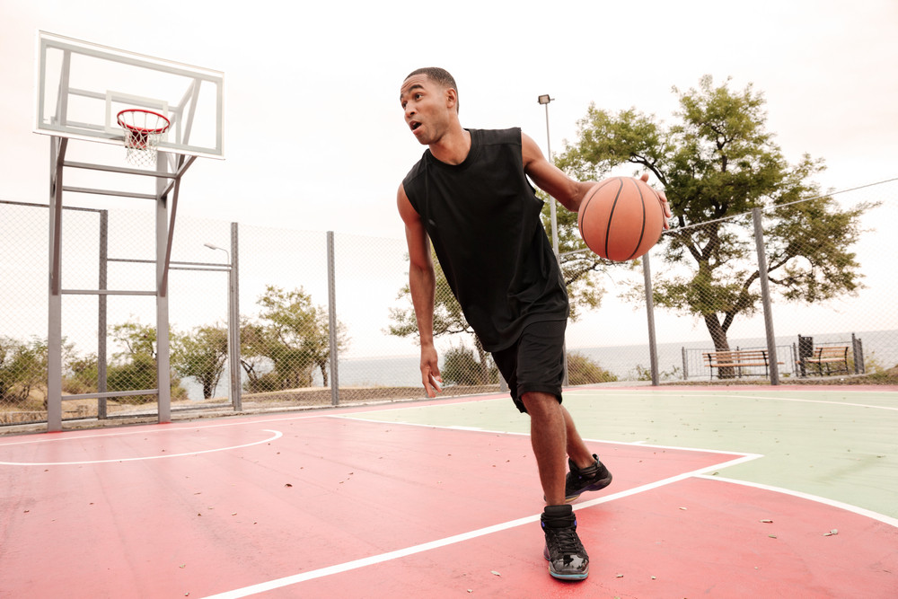 Picture of young confused african basketball player practicing. Looking aside.