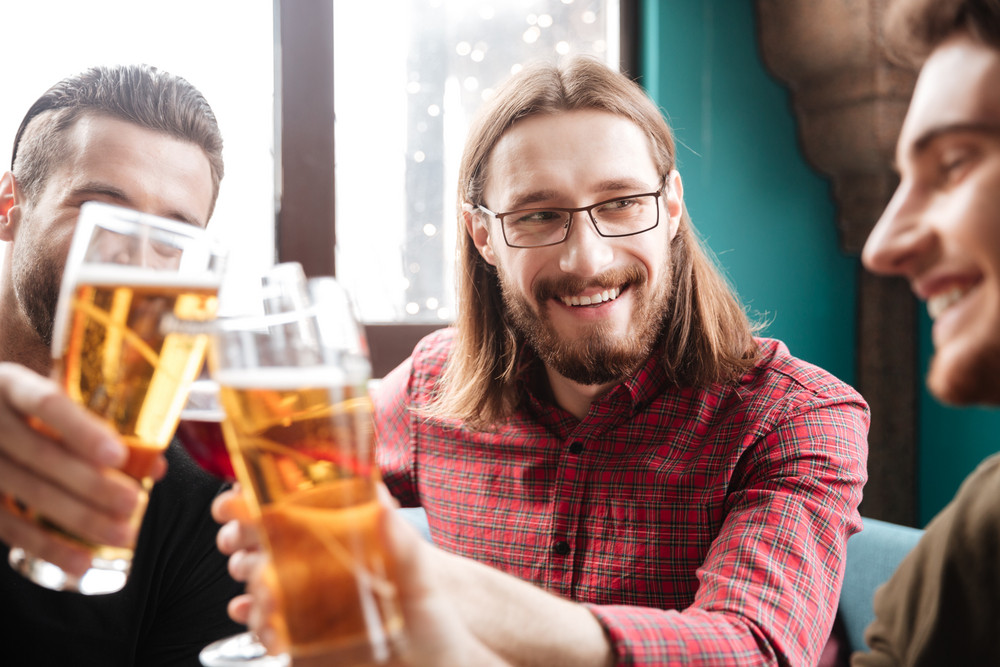 Picture of young happy friends sitting in cafe while drinking alcohol. Looking at each other.