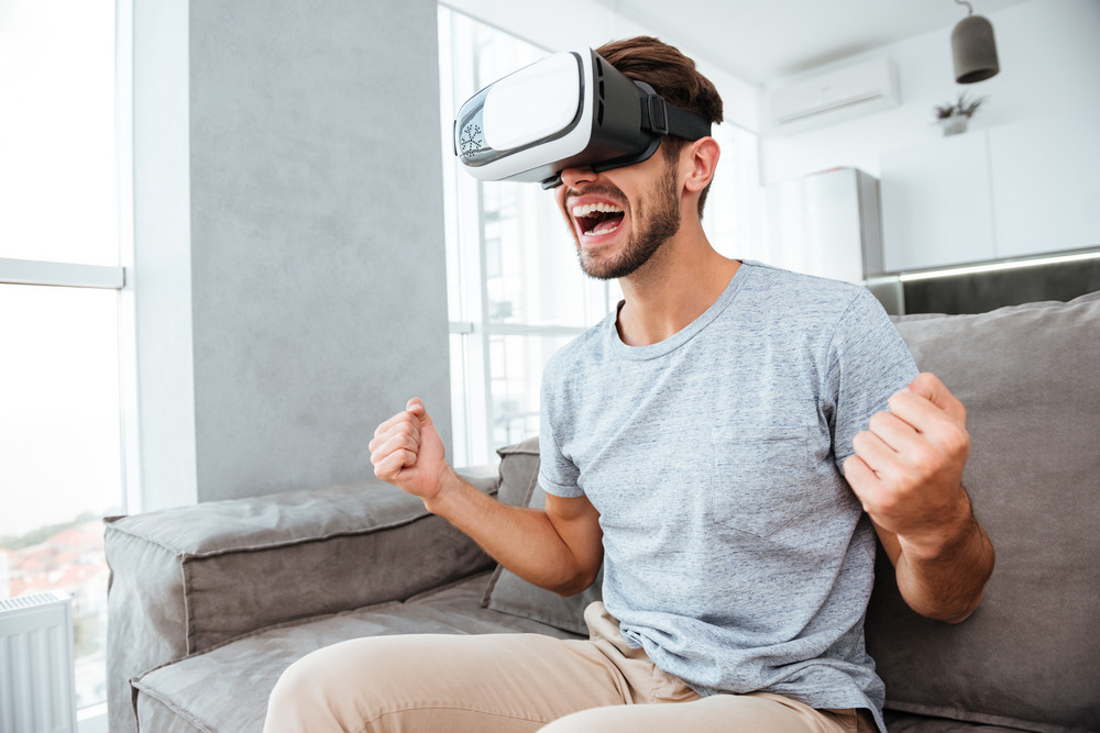 Picture of young happy man making winner gesture while wearing virtual reality device and sitting on sofa.