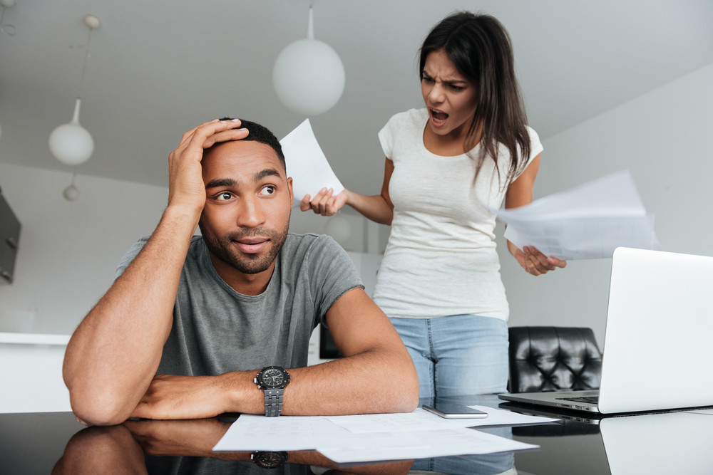 Picture of young loving couple discussing about domestic bills at home. Woman screaming to man while holding documents.