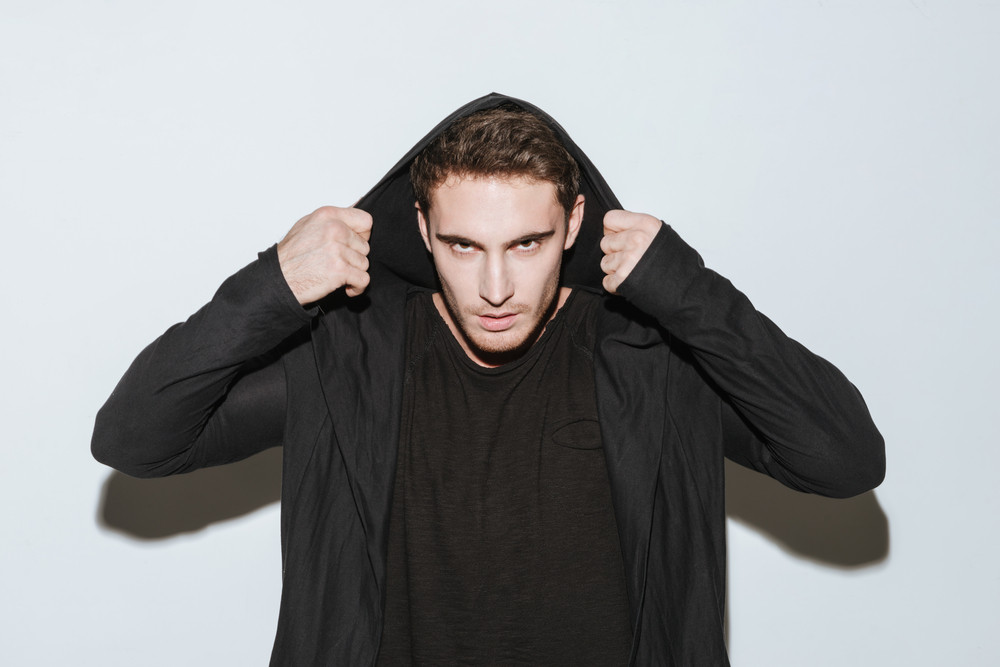 Picture of young man dressed in black t-shirt and mantle standing over white background and posing.