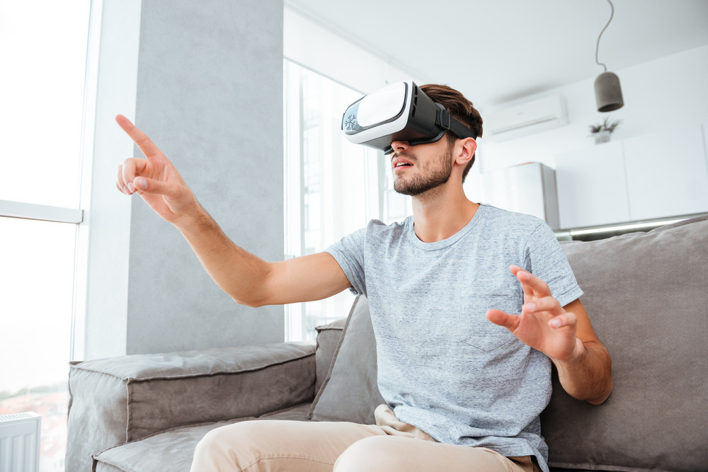 Picture of young man dressed in grey t-shirt wearing virtual reality device while sitting on sofa and pointing