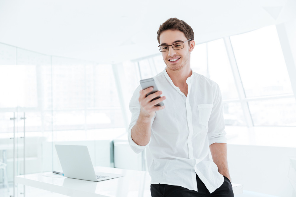 Picture of young man dressed in white shirt chatting by phone. Looking at phone.