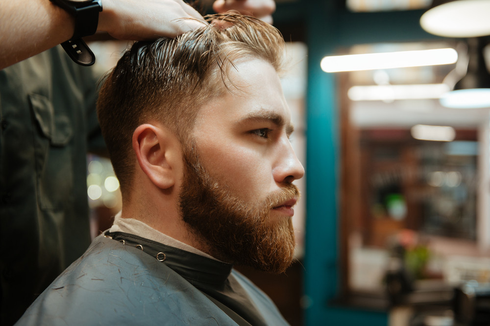 Picture Of Young Man Getting Haircut By Hairdresser With Scissors