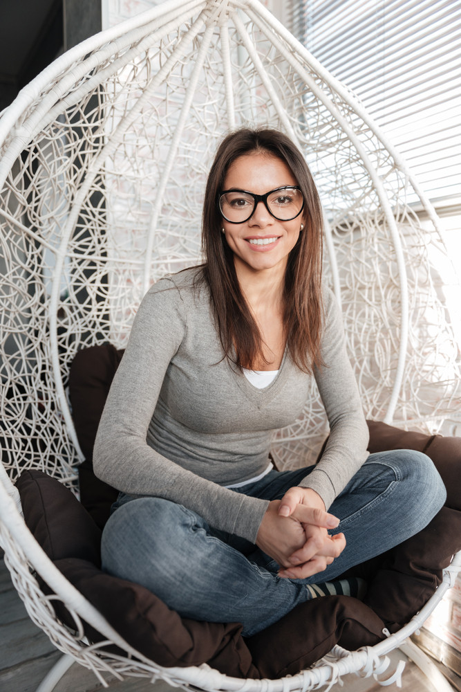 Picture of young pretty lady wearing eyeglasses sitting on chair indoors. Look at camera.