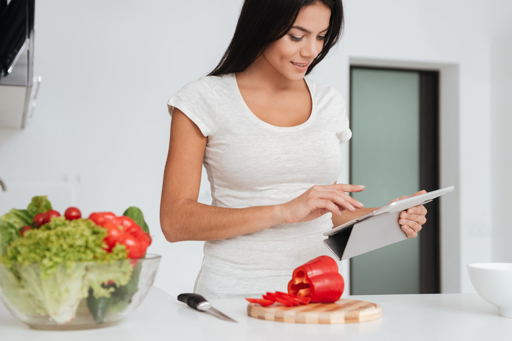 Picture of young pretty woman reading recipe from tablet computer in the kitchen. Looking at tablet computer.