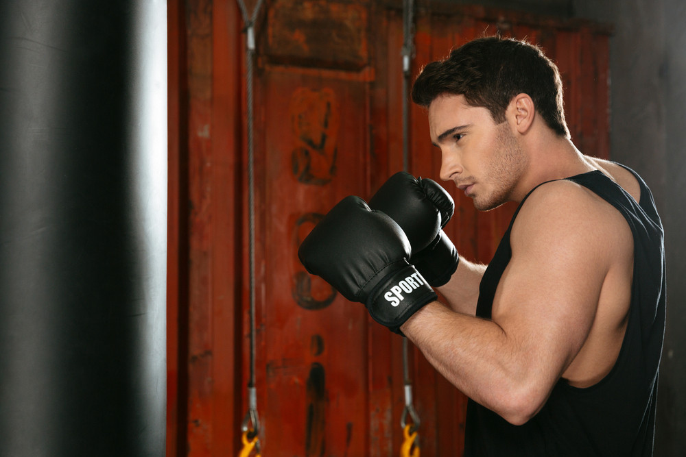Picture of young strong boxer training in a gym with punchbag. Looking at punchbag.