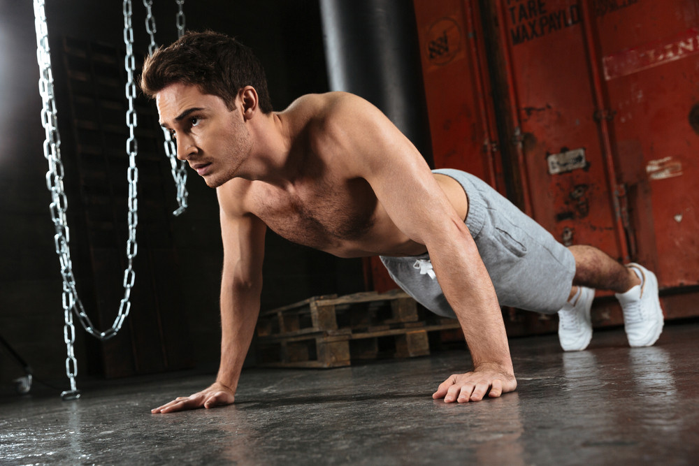 Picture of young strong man make sport exercises in a gym. Looking aside.