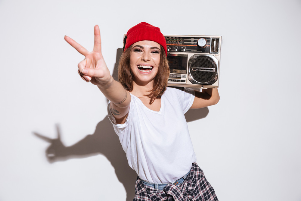 Picture of young woman dressed in white t-shirt standing isolated over white background while holding tape recorder and make peace gesture.