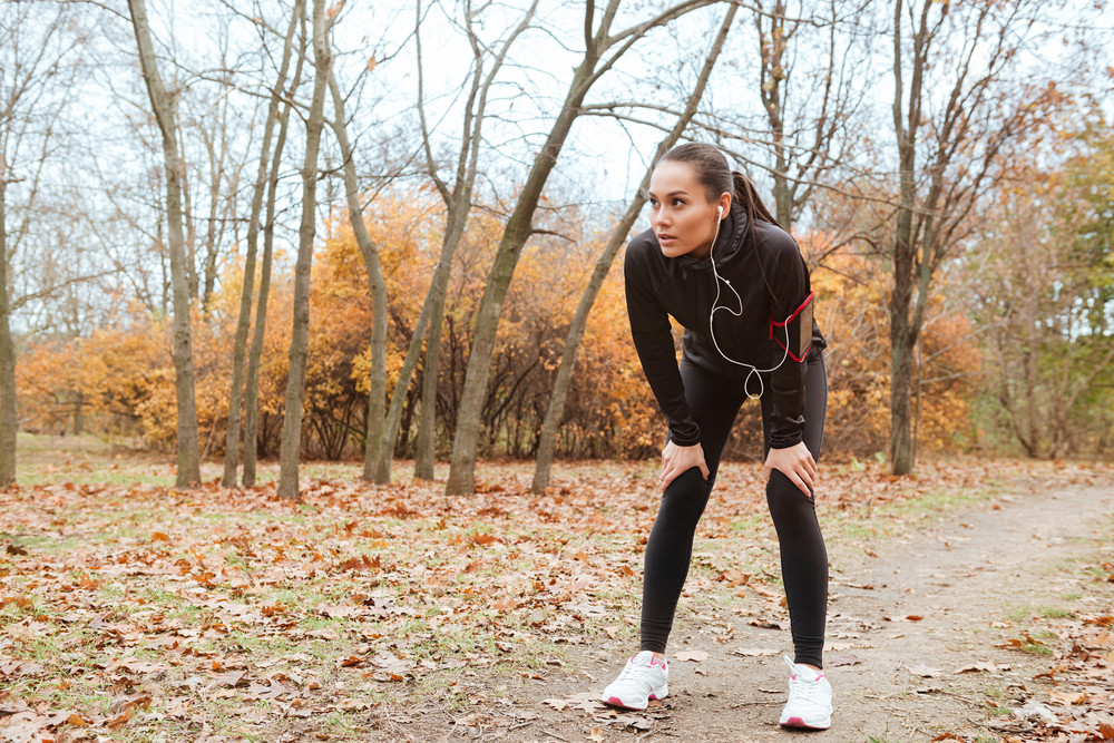 Picture of young woman runner in warm clothes and earphones running in autumn park