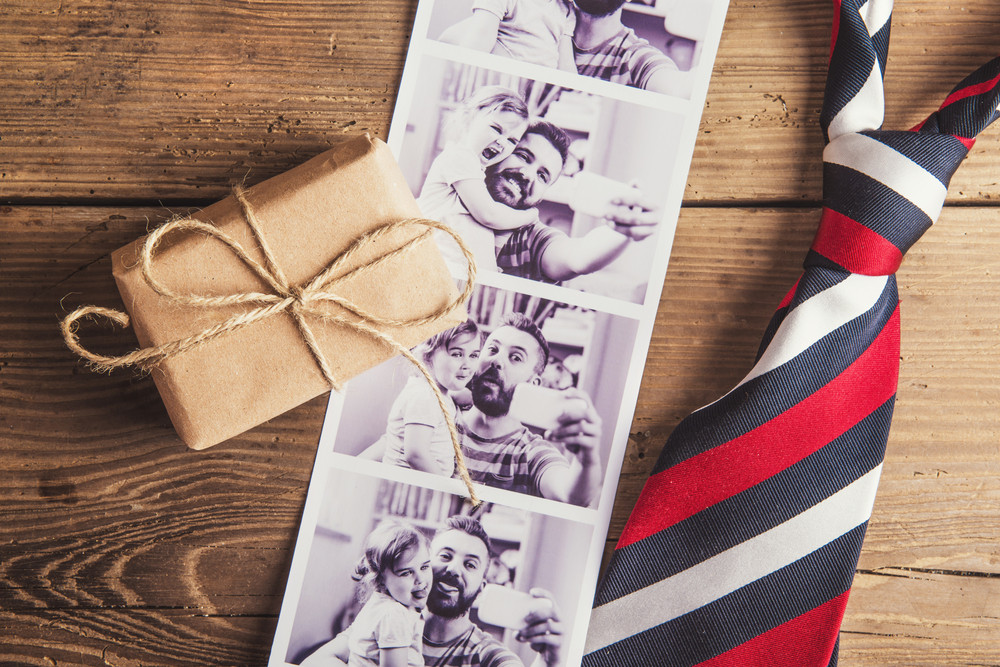 Pictures of father and daughter, little box and colorful tie laid on wooden floor background.