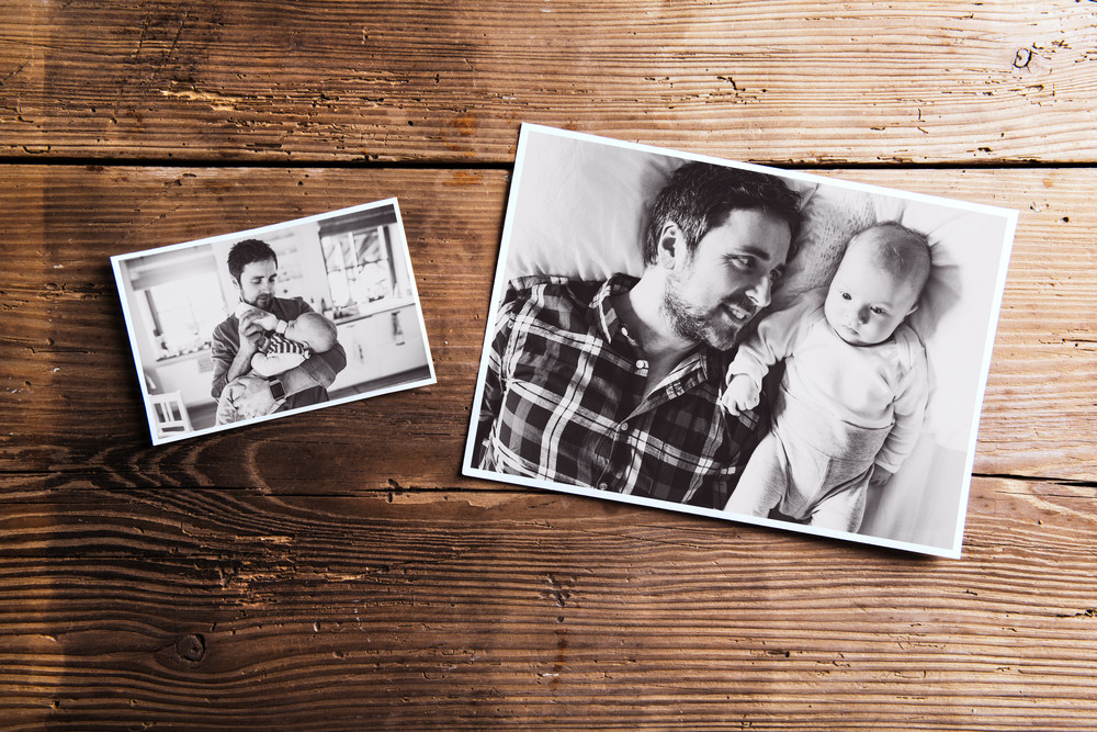Pictures of young father and his cute newborn baby son laid on table ...