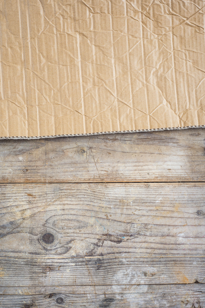 Piece of carton on wooden floor background