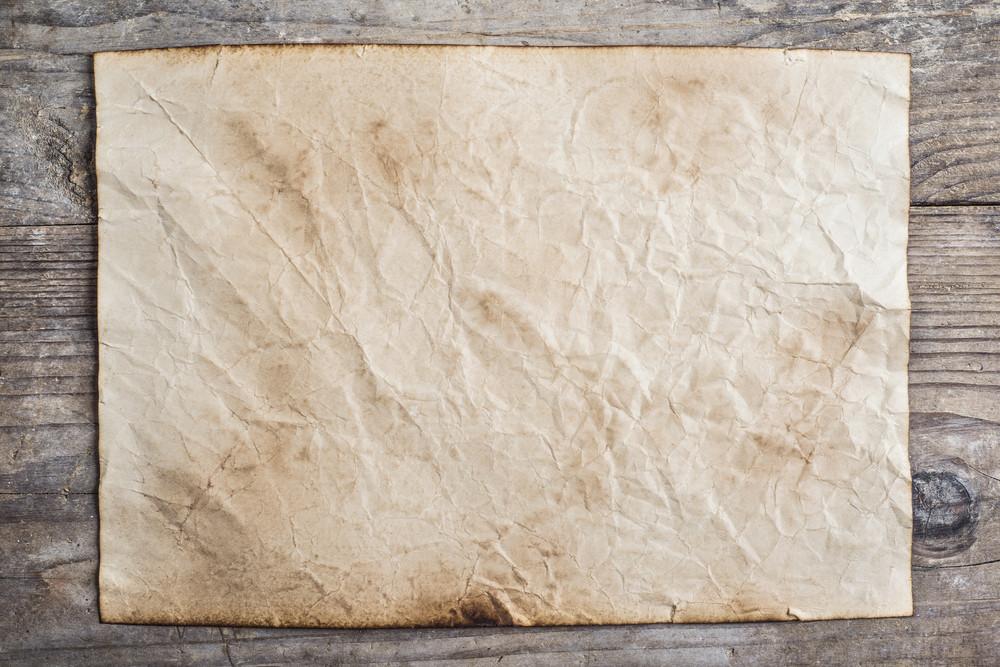 Piece of old rumpled paper on wooden floor background