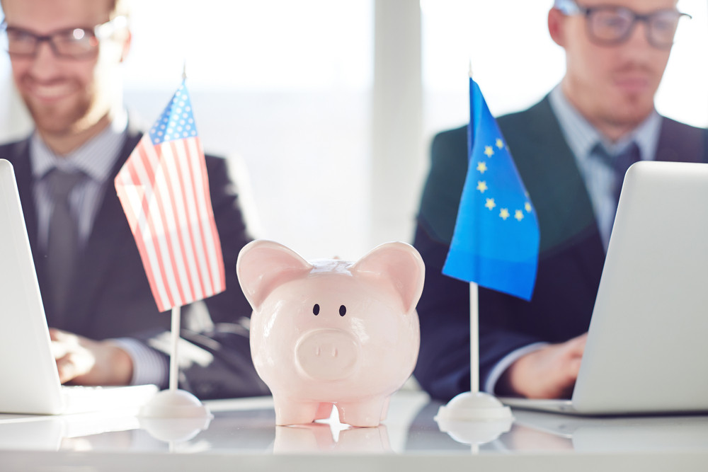 Piggy bank between eu and American flags on background of working colleagues