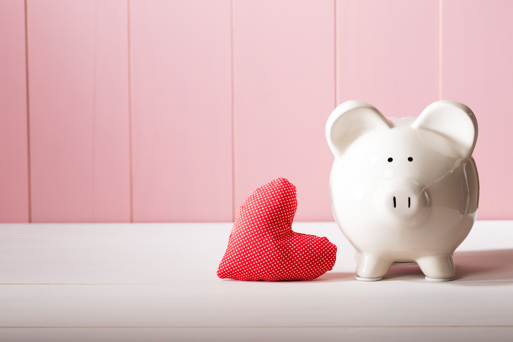 Piggy bank with red heart pillow on pink wooden wall