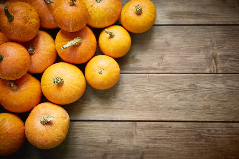 Pile of orange pumpkins on wooden table