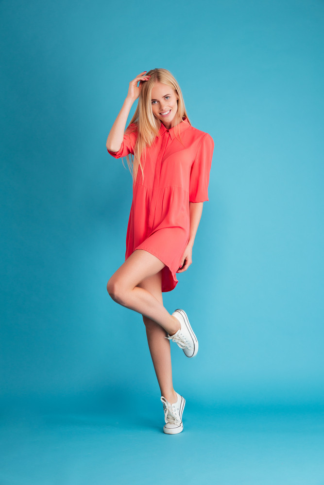Playful pretty young woman with long hair in red dress posing on one leg isolated on a blue background
