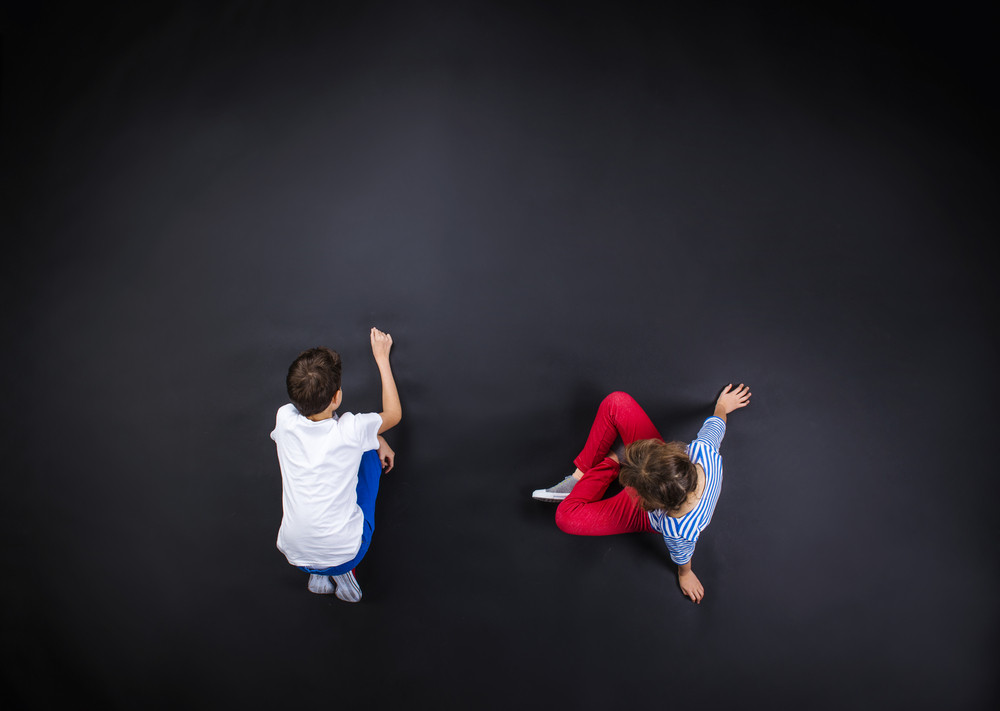 Playful young siblings having fun together as they prepare to go back to school. Studio shot on a black background.