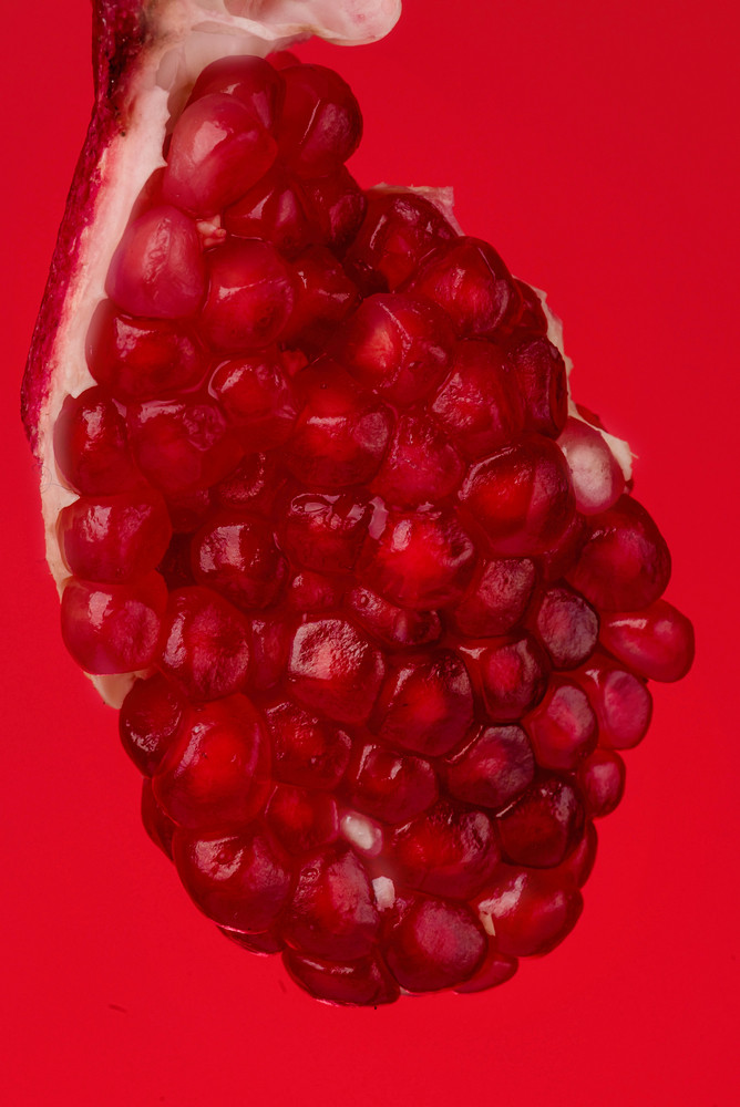 Pomegranate piece isolated on red background