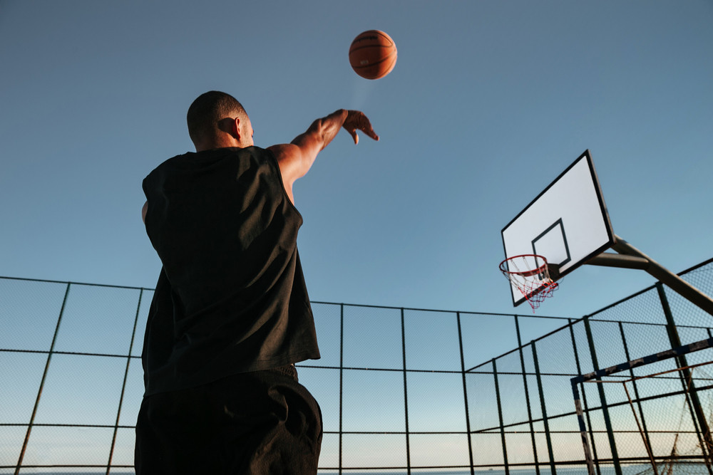 Portrait of a basketball player taking a jump shot on an outdoor basketball court