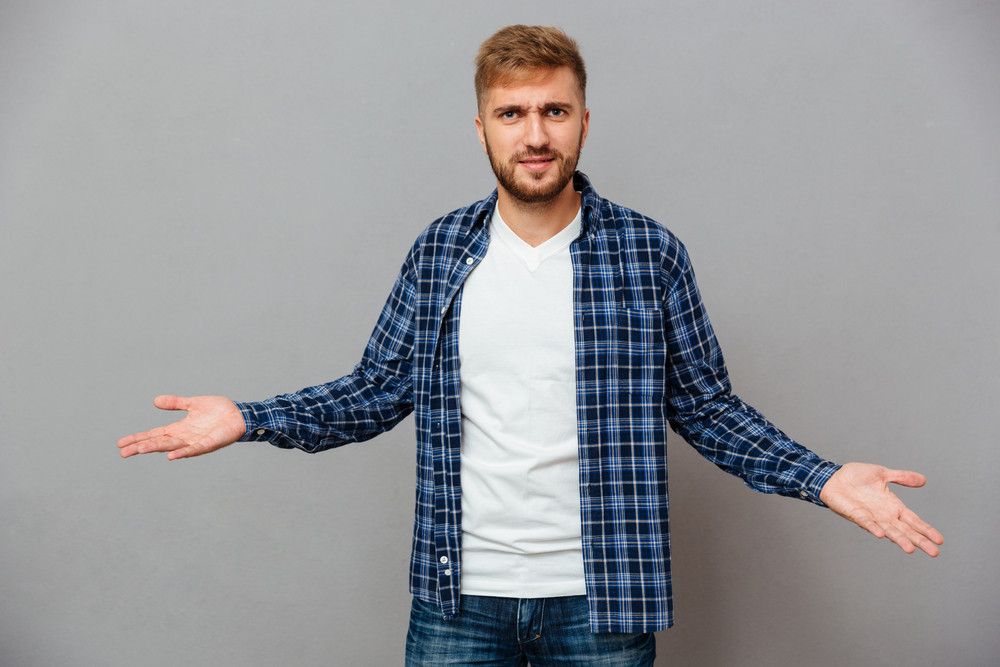 Portrait of a bearded casual man shrugging shoulders isolated on a gray background