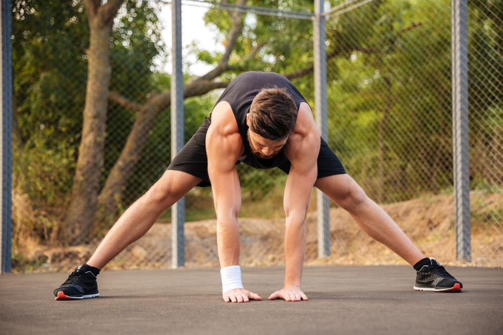 Portrait of a bearded young man in sportswear stretching legs outdoors