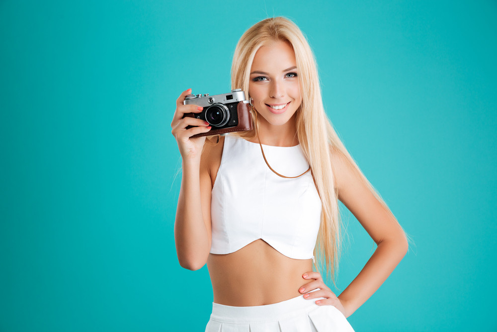 Portrait of a beautiful blonde woman holding photo camera and looking at camera isolated on the blue background